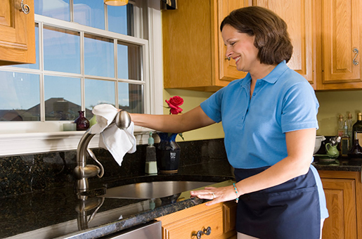 A carer cleaning the kitchen tap