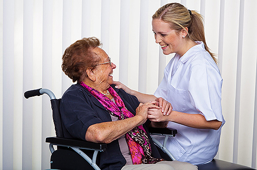 A carer laughing with a lady in a wheel chair.