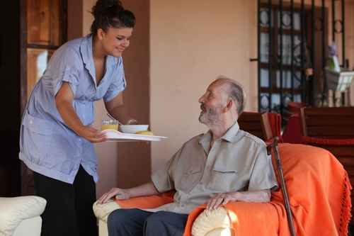A client being served a meal by a carer